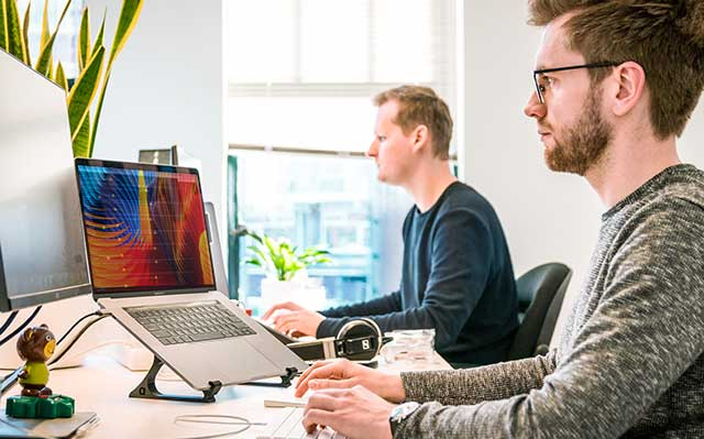Two Website Designers sit at their workstations in the process of creating responsive mobile websites