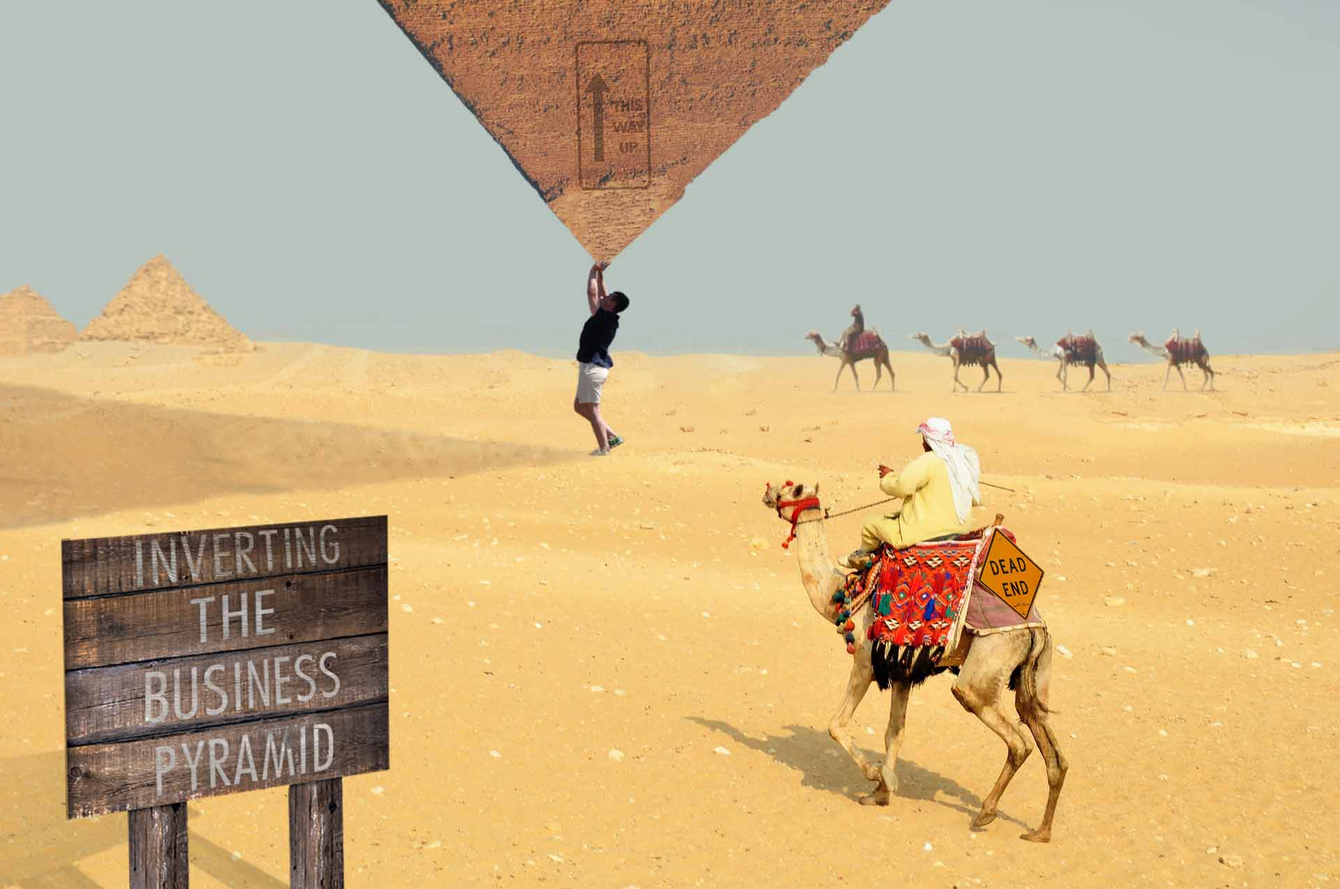 Standing in the desert lifting and inverting the big business pyramid upside down amongst the surprised camel riders